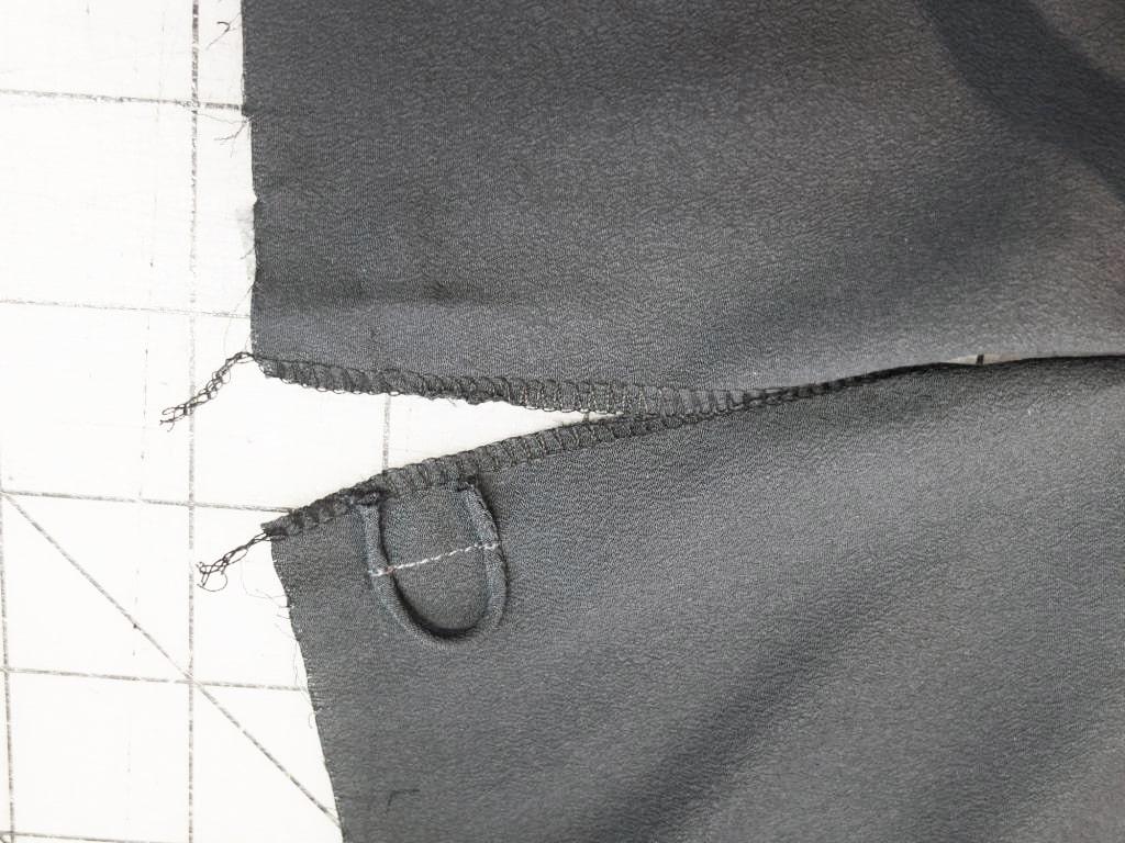Der rückwärtige Schlitz einer Bluse ist zu sehen. Die Schlaufe ist angenäht.