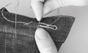 Mit Nadel und Faden wird per Hand ein Knopfloch durch enge Stiche verstärkt.