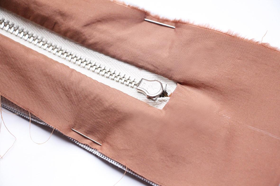 Die Abbildung zeigt die Verarbeitung einer Gürteltasche. Hier das Einnähen des Reißverschlusses.