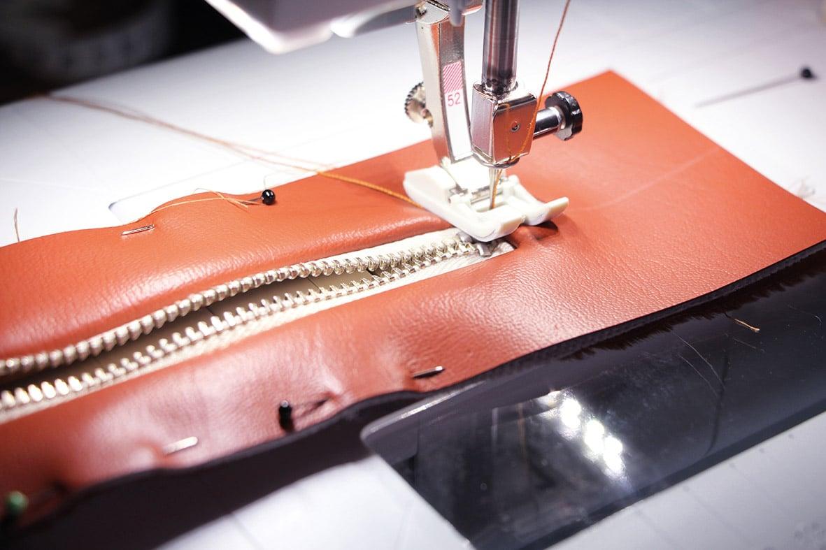Die Abbildung zeigt die Verarbeitung einer Gürteltasche. Hier das Absteppen des Reißverschlusses.