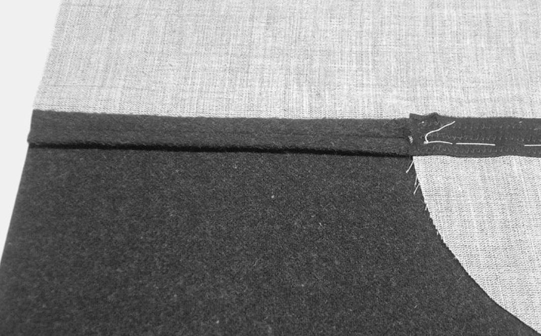 Das Vorderteil wird mit der Einlage hinterlegt und an den Flankennähten sowie den Außenkanten der Einlage zusammengeheftet. Im unteren Bereich der Flankennaht wird die Einlage mit Kreuzstichen befestigt.