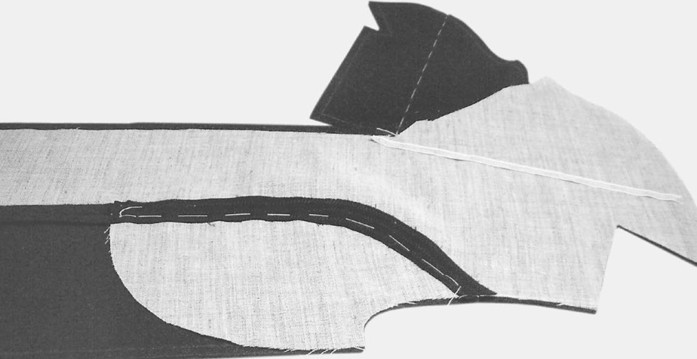 Die Einlage wird wie folgt zurückgeschnitten: vordere Kante, Kragenkante und Halsloch bis zur Nahtlinie; Armloch und Schulter an die Schnittkante des Oberstoffes angleichen.
