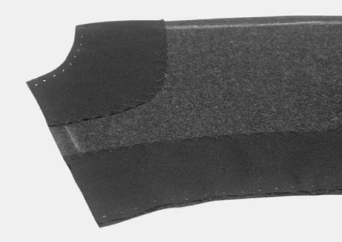 Im Rückenteil werden die Flankennähte genäht, Hals- und Armloch mit Belegen aus Baumwolle hinterlegt und mit Kreuzstichen fixiert.