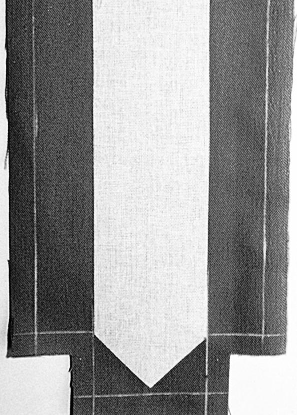 Das Foto zeigt die Schablone einer Gürtelspitze auf dem Stoff platziert.