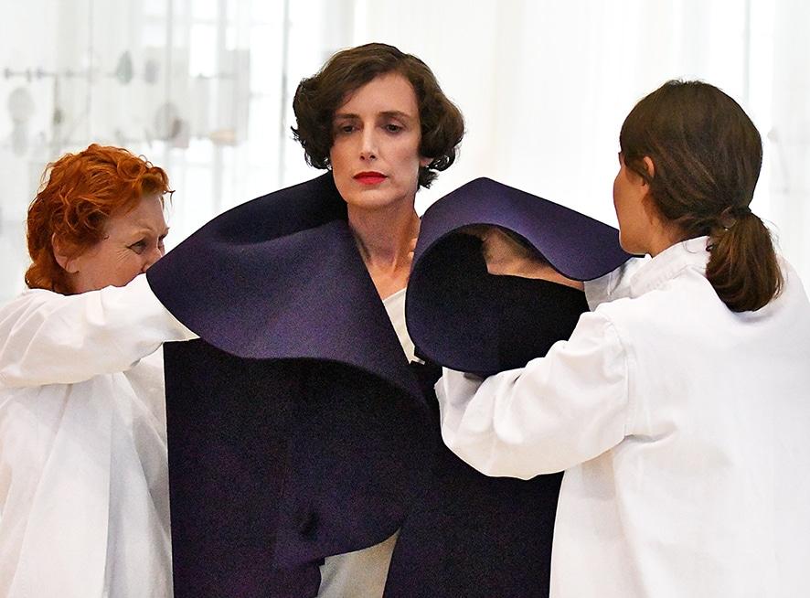 Bild einer Frau an der ein Kragen drapiert wird.