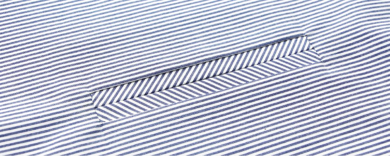 Abgebildet ist die Verarbeitung einer Paspeltasche. Gezeigt wird die Nähanleitung aus gestreiftem Stoff.