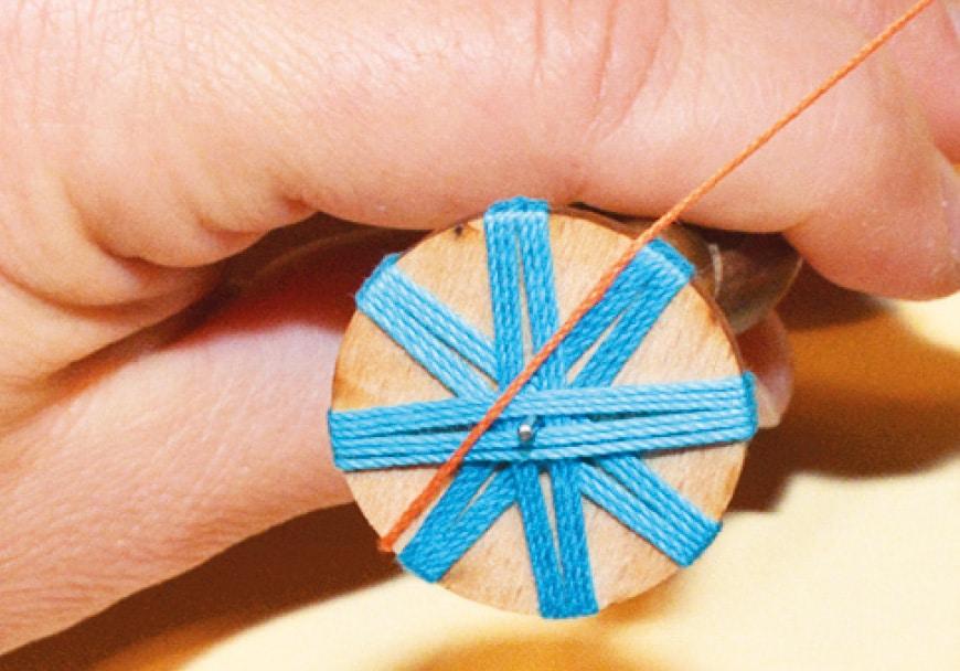 Gezeigt wird die Verarbeitung eines Posamentenknopfes mit Nadel und Faden.