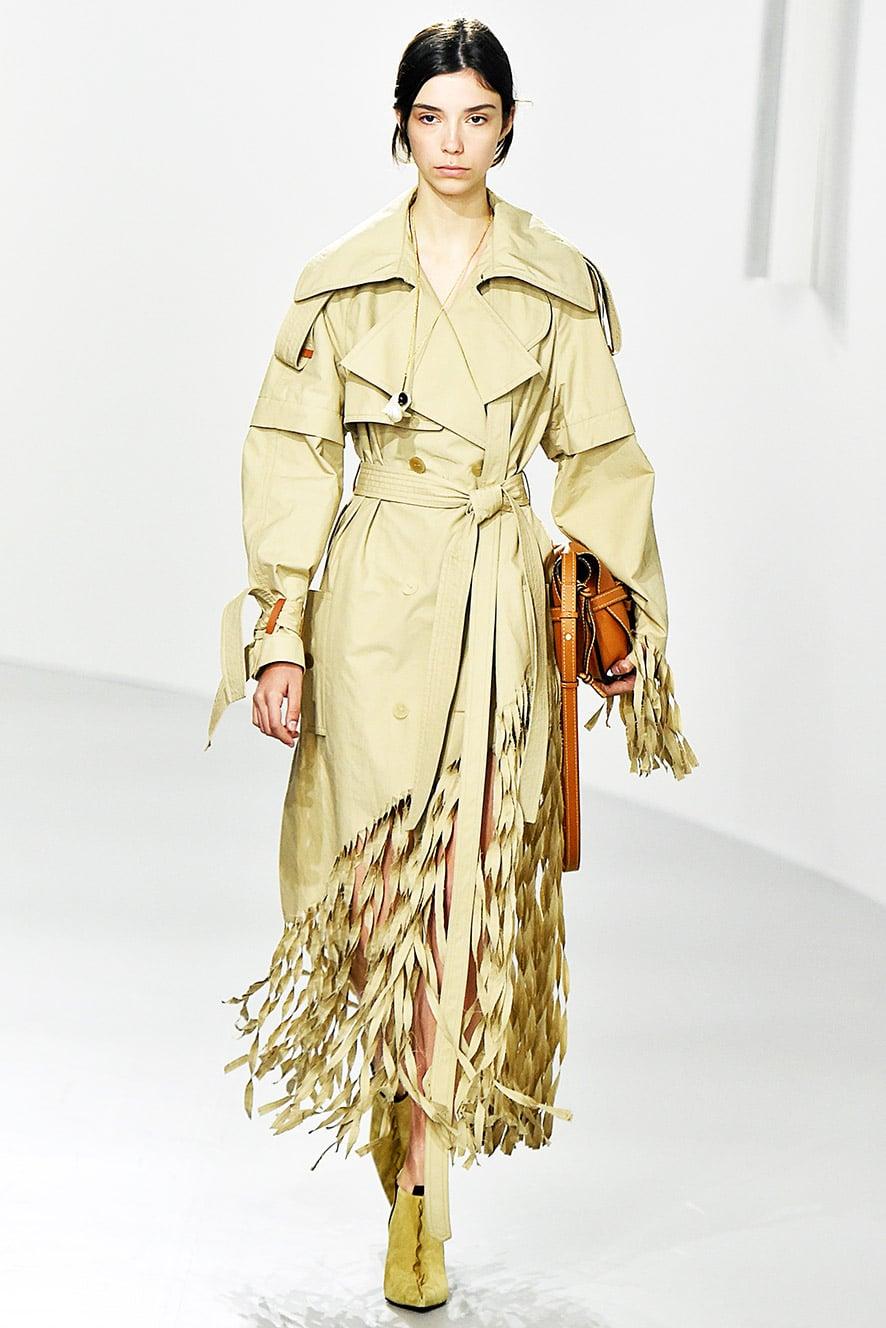 Das Foto zeigt ein Model auf dem Catwalk die einen Trenchcoat trägt. Die Fotos dienen als Vorlage für den Mantel auf dem Schnittmuster