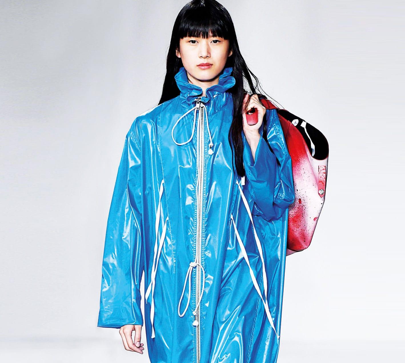 Zu sehen ist ein Model mit blauer Regnejacke. Bezogen auf die Stofftrends 2019.