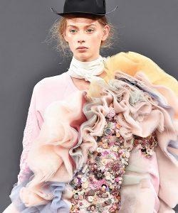 Ein Laufstegmodel trägt ein dicht mit diversen Knöpfen besetztes Kleidungsstück.