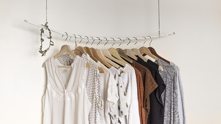 Eine Kleiderstange auf der verschiedene Kleidungsstücke hängen.