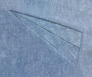 Spitz zulaufende Paspeltasche auf blauem Stoff