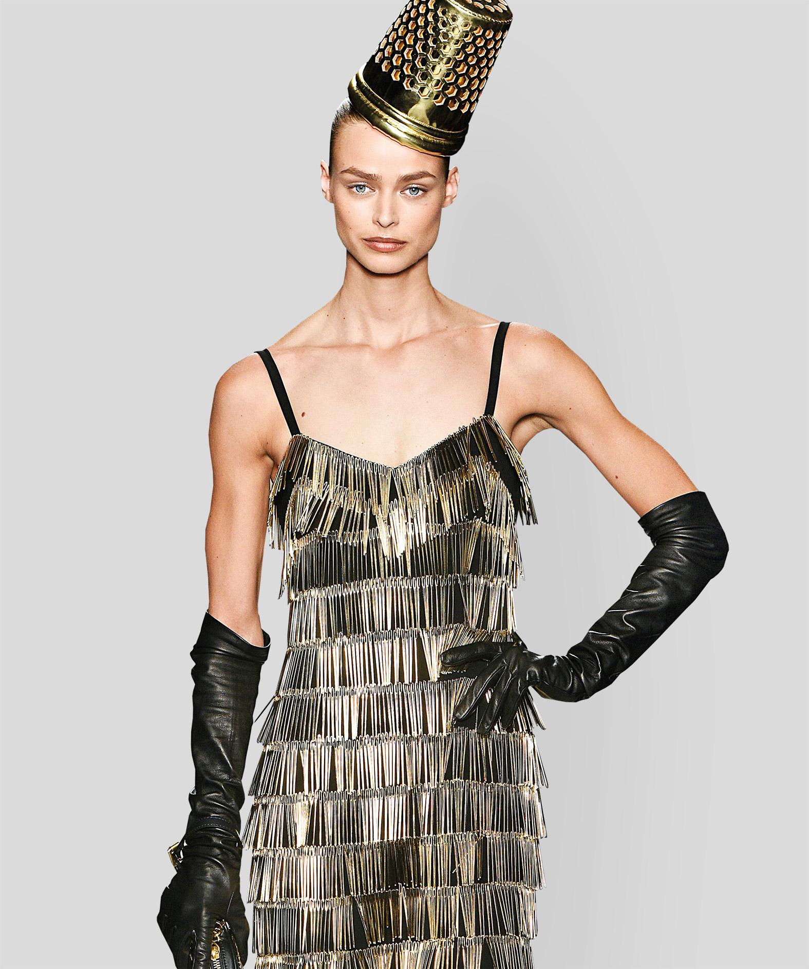 Modell von Moschino auf dem Laufsteg, mit Fingerhut aus dem Kopf und Kleid aus Nadeln.