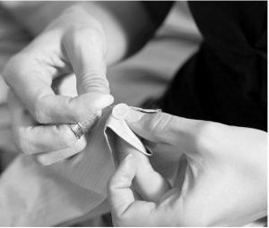 Zwei Hände nähen einen Knopf an ein Kleidungsstück