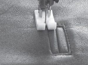 Die Nähnadel einer Nähmaschine steht auf einer Taschennaht auf Leder