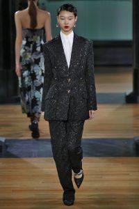 Laufsteg-Model trägt übergroßen dunkel gemusterten Hosenanzug im Stil der 20er.