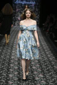 Laufsteg-Model trägt knielanges, wallendes Kleid mit blauem Floralmuster im Stil der 60er.