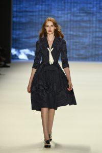 Laufsteg-Model trägt knielanges Kleid mit V-Ausschnitt und ausgestelltem Rock im Stil der 40er.