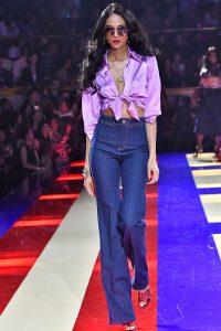 Laufsteg-Model trägt dunkelblaue Schlaghose mit seidiger bauchfreier Bluse im Stil der 70er.