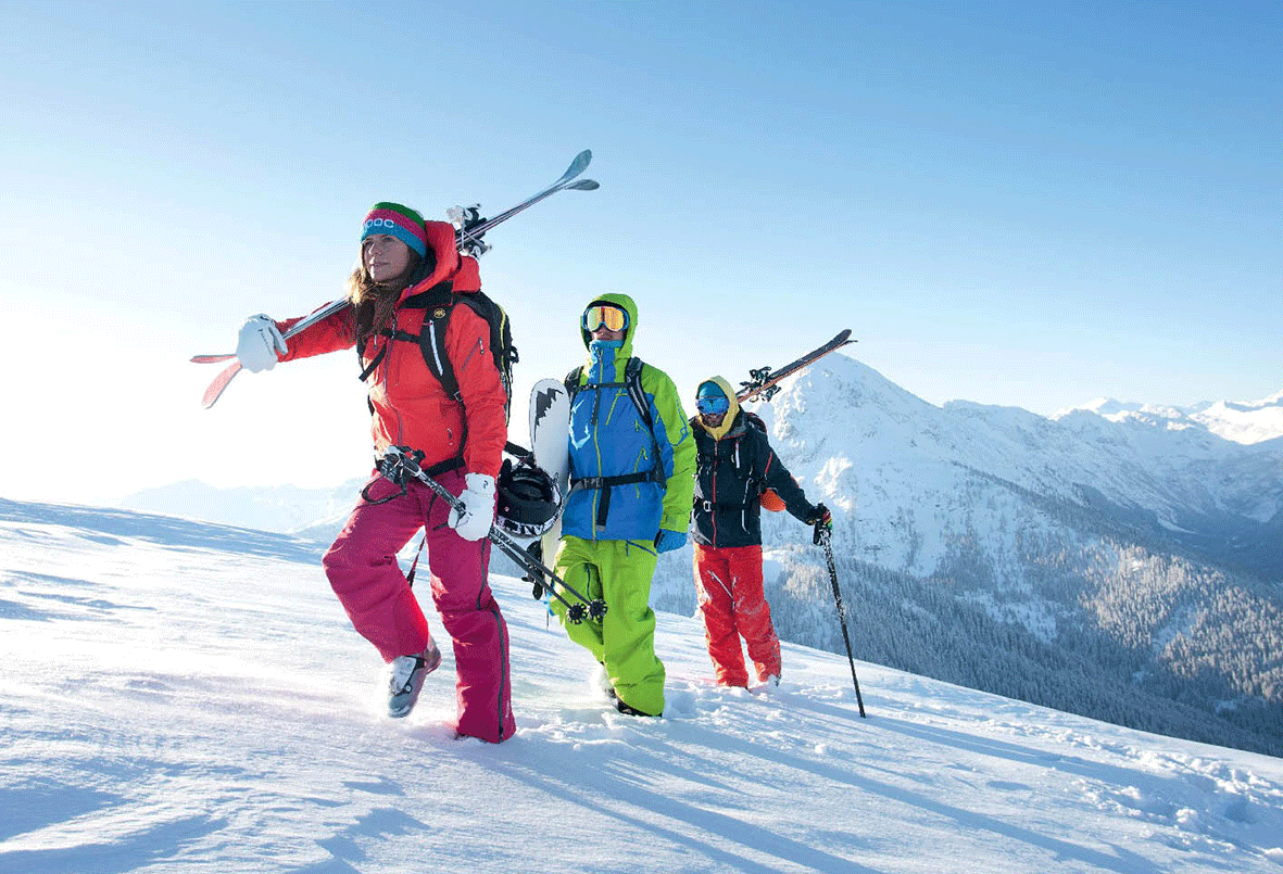 Skiers and snowboarders in ski fashion in strong colours