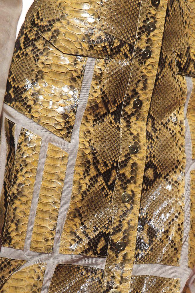 Ausschnitt von einem gelben Lederrock mit Schlangenmuster.