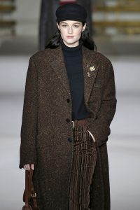 Model trägt langen Mantel aus Tweed-Stoff mit Fischgrätmuster
