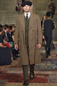 Model trägt langen Mantel aus Tweed-Stoff.