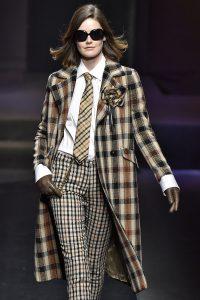 Model trägt langen Mantel im Tartanmuster.