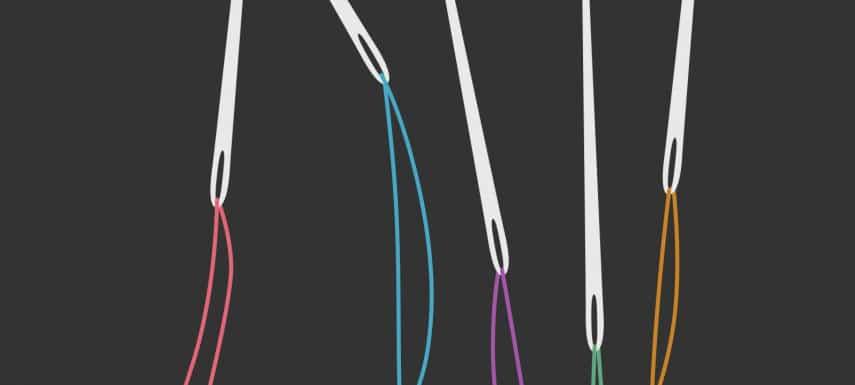 Vier verschiedene Nähnadeln mit Faden